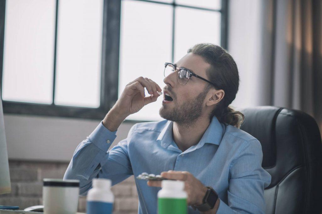 Homme barbu à lunettes prenant une gélule de cbd