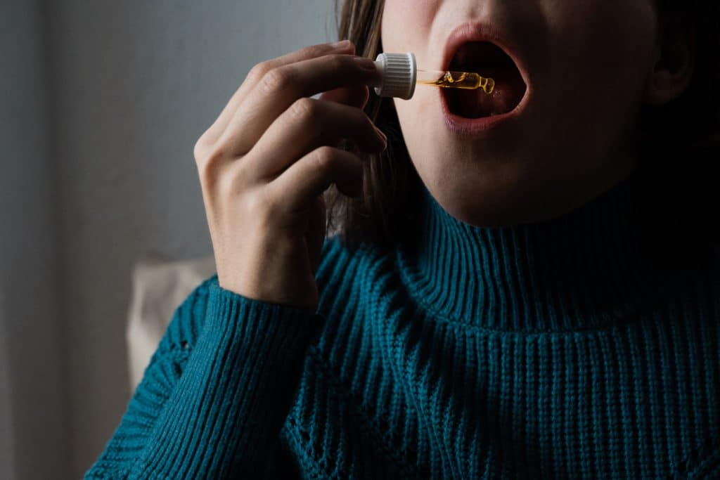 Cbd hemp oil - Woman taking sublingual cannabis oil medicine - Supplement and alternative medicine