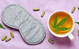 Concept de sommeil nocturne sain. Masque de sommeil, thé de chanvre calmant et capsules de chanvre sur bandeau de soie lilas.